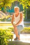 Grey Bearded Old Man en chaleco puso a Bent Leg en banco en parque imagen de archivo libre de regalías