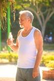Grey Bearded Old Man en chaleco sostiene la botella de agua en parque imágenes de archivo libres de regalías