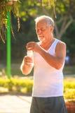 Grey Bearded Old Man en chaleco sostiene la botella de agua en parque imagen de archivo