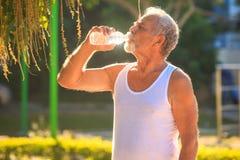 Grey Bearded Old Man en chaleco sostiene la botella de agua en parque foto de archivo