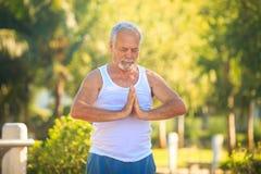 Grey Bearded Old Man en el chaleco blanco muestra yoga en parque foto de archivo