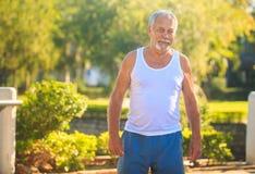 Grey Bearded Old Man en los soportes blancos del chaleco sonríe en parque fotografía de archivo libre de regalías