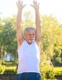 Grey Bearded Old Man in Vest heft Handen op omhoog glimlacht in Park stock afbeeldingen