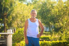 Grey Bearded Old Man in White Vest Bends Body in Park Stock Photography