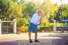 Grey Bearded Old Man in Wit Vest buigt Lichaam in Park stock afbeeldingen