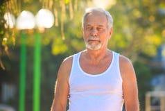 Grey Bearded Old Man in Wit Vest toont de Yoga in Park stelt royalty-vrije stock fotografie