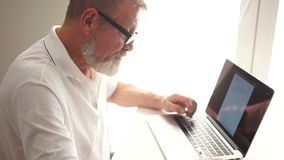 The grey-bearded writer is writing a book with the help of a laptop. Mature man works with laptop at home
