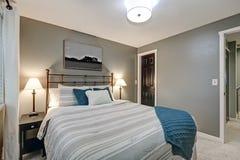 Grey bedroom boasts large iron bed Stock Photo
