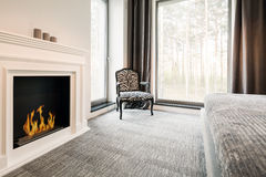 Grey bedroom with elegant fireplace Royalty Free Stock Photos