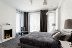 Grey bedroom with fireplace and bed stock photography