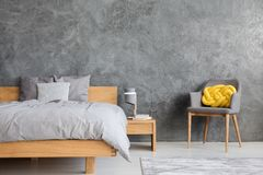 Grey bedroom with armchair. Grey bedroom interior with king size bed, armchair and yellow knot cushion Stock Photography