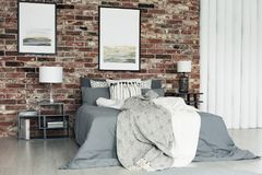 Paintings in grey bedroom. Grey bedsheets on king-size bed between nightstands with lamps against brick wall with paintings in bedroom Stock Image