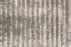 Grey-beige wall with a decorative plaster and vertical stripes. Surface of the wall with a decorative grey - beige plaster. Textured concrete wall with vertical royalty free stock photo