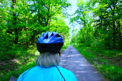 Grey Biking. Senior woman biker on pleasant forest bike trail Royalty Free Stock Images