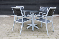 Grey and black chairs with table on stone patio Stock Images
