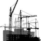 Grey and black cranes and house buildings Stock Photography