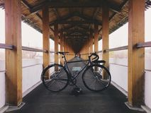Grey-black fixie bicycle in the wooden path Stock Photo