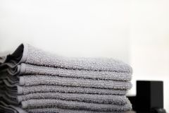 Grey towels towels are on the bathroom floor. Towels hung on hooks. royalty free stock image