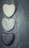Grey,black,white zen hearts shaped rock on a tile background Stock Image