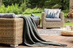 Grey blanket on rattan sofa near armchair with pillows on wooden. Terrace with pouf. Real photo royalty free stock image