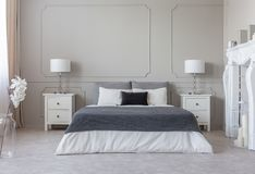 Grey blanket on white bedding on comfortable king size bed, two nightstand with lamps on both sides of it. Real photo concept royalty free stock images