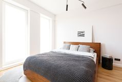 Grey blanket on wooden bed in white bright bedroom interior with. Simple poster. Real photo royalty free stock images