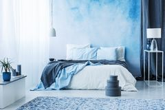 Grey boxes next to bed with blue bedding in bedroom interior wit royalty free stock image