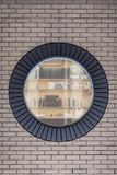 Brick wall with round window. Grey brick wall with round window looking inside to room with book shelves Royalty Free Stock Image