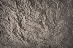 Grey-brown crumpled wrapping paper background, texture of grey wrinkled of old vintage paper, creases on the surface of gray paper.  royalty free stock photos