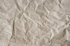 Grey-brown crumpled wrapping paper background, texture of grey wrinkled of old vintage paper. Creases on the surface of gray paper royalty free stock photography