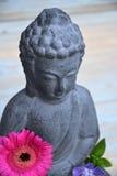 Grey Buddha-Statue mit Blumen und Zensteinen Lizenzfreie Stockbilder