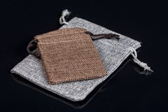 Grey burlap jute drawstring gift jewelry pouches bag  above black background with reflections Stock Photography
