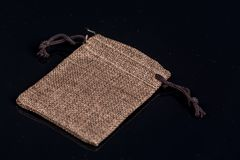 Grey burlap jute drawstring gift jewelry pouches bag  above black background with reflections Stock Photos