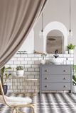 Grey cabinet with washbasin in modern bathroom interior with drapes and mirror. Real photo royalty free stock images