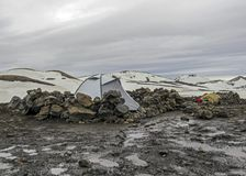 Grey camping tent in Hrafntinnusker campsite in bad weather conditions, Laugavegur hike, Fjallabak Nature Reserve, Highlands of stock photo