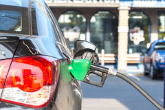 Grey car at gas station being filled with fuel Royalty Free Stock Photo