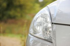 Grey car part, car headlight. daily lights. Green background, village. royalty free stock photos
