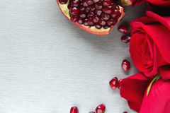 Grey card with red roses and sliced pomegranate Royalty Free Stock Image
