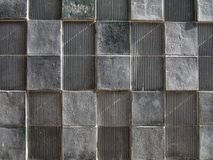 Grey concrete wall with geometric square pattern and distressed textures. A grey cast concrete wall with geometric square pattern and distressed textures stock image