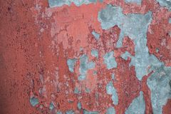 Grey cement wall with peeling, weathered red paint texture. Rustic background with scratches and marks royalty free stock photography