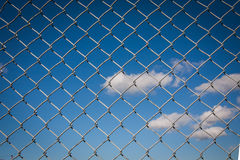 Grey Chain Link Fence. Detailed grey chain link, wire mesh fence with a blue sky and white clouds background royalty free stock photos