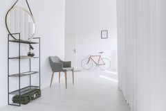 Grey chair in minimalist corridor. Mirror on shelf next to grey chair in minimalist corridor with red bicycle against wall with poster Royalty Free Stock Images