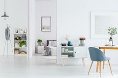 White open space interior. Grey chair at wooden table in white open space interior with poster on the wall and bright bedroom Royalty Free Stock Photos