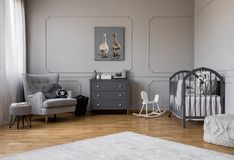 Free Grey Chest Of Drawers In The Middle Of Elegant Grey Baby Room With Comfortable Armchair And Wooden Cradle Royalty Free Stock Photo - 140831175