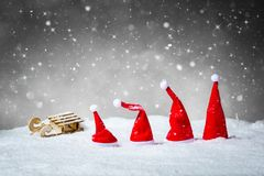 Grey Christmas Background With Santa Hats and Sled in snow.  Stock Photos