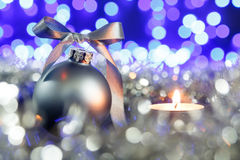 Grey christmas ball and candle, blured purple lights at the background Stock Image
