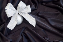 Grey Christmas ball with silver bow on black flowing fabric Stock Images