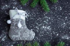 Grey Christmas stocking on snowbound black background with fir b Stock Photos