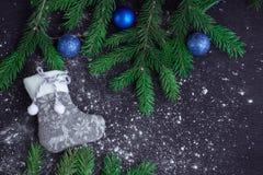 Grey Christmas-Strumpf auf eingeschneitem schwarzem Hintergrund, blauer Ball Stockfoto