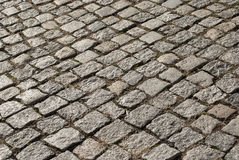 Grey city pavement. Granite gray town pavement close-up as background diagonal view royalty free stock images